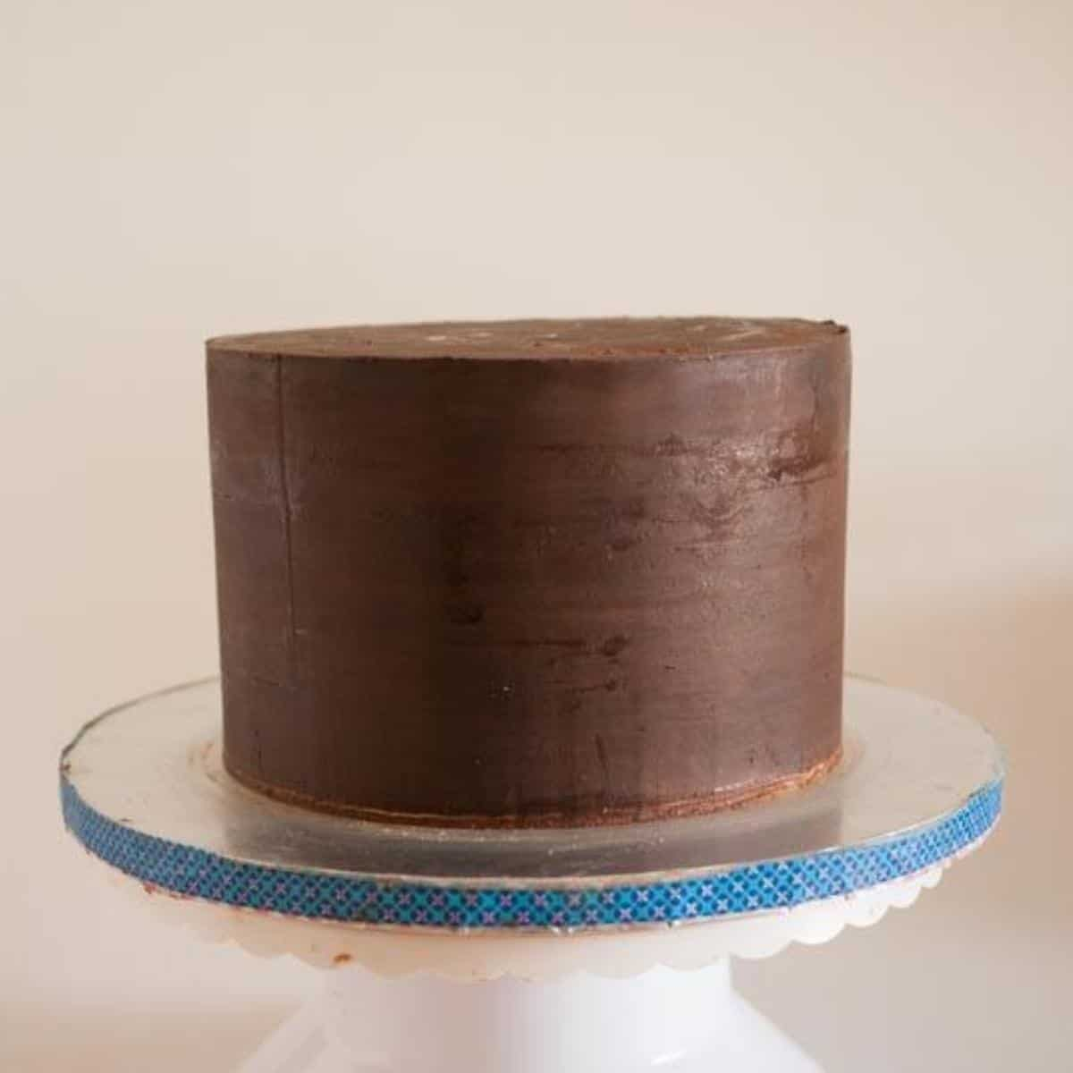 A cake with sharp edges covered in ganache.