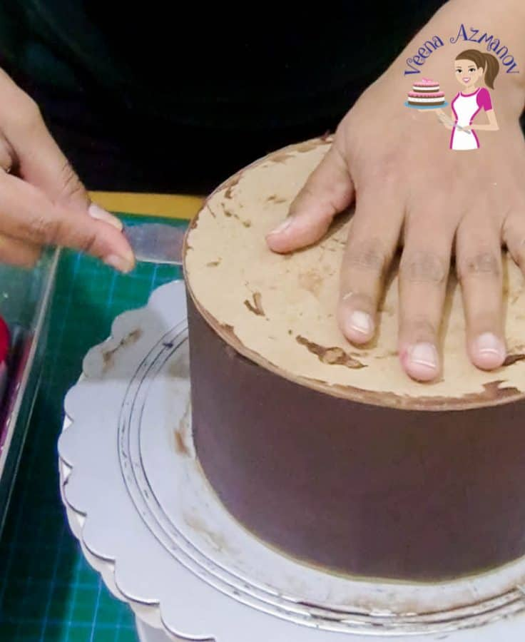 A person covering a cake with ganache.