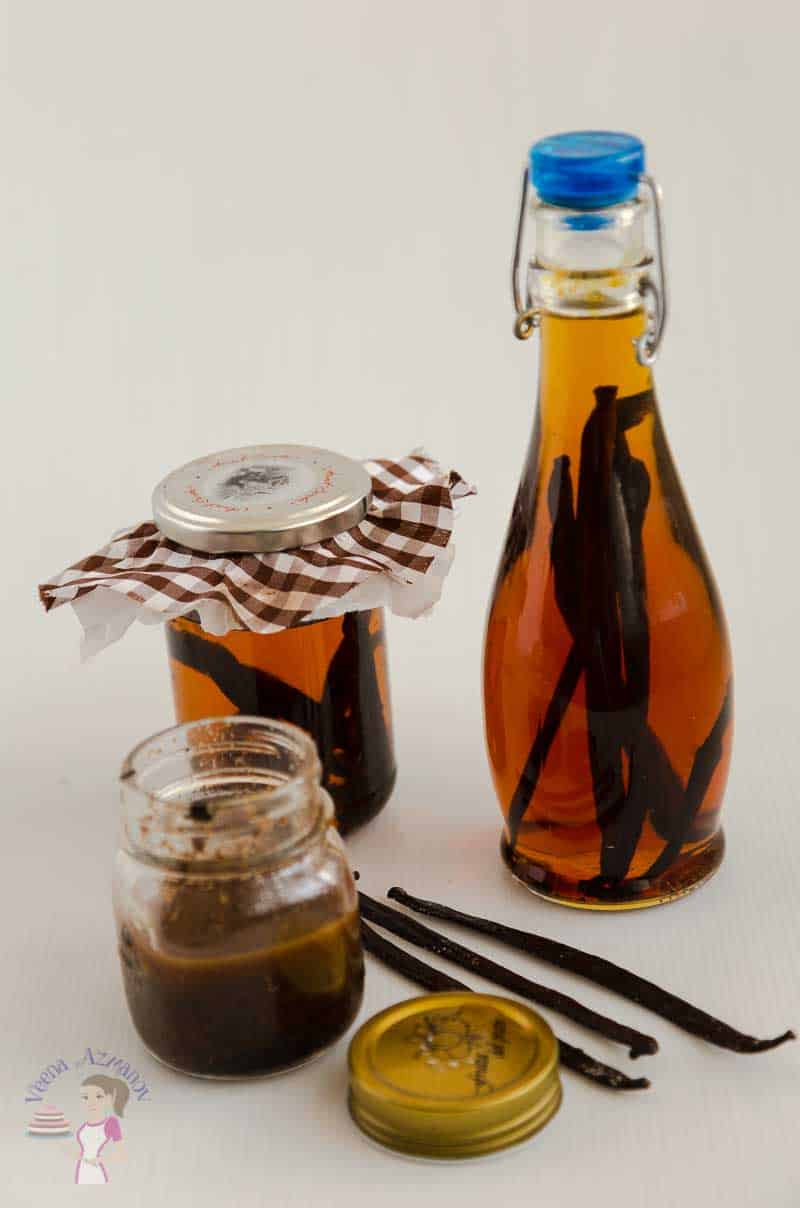 An image showing two jars of homemade vanilla extract and a jar of vanilla bean paste.
