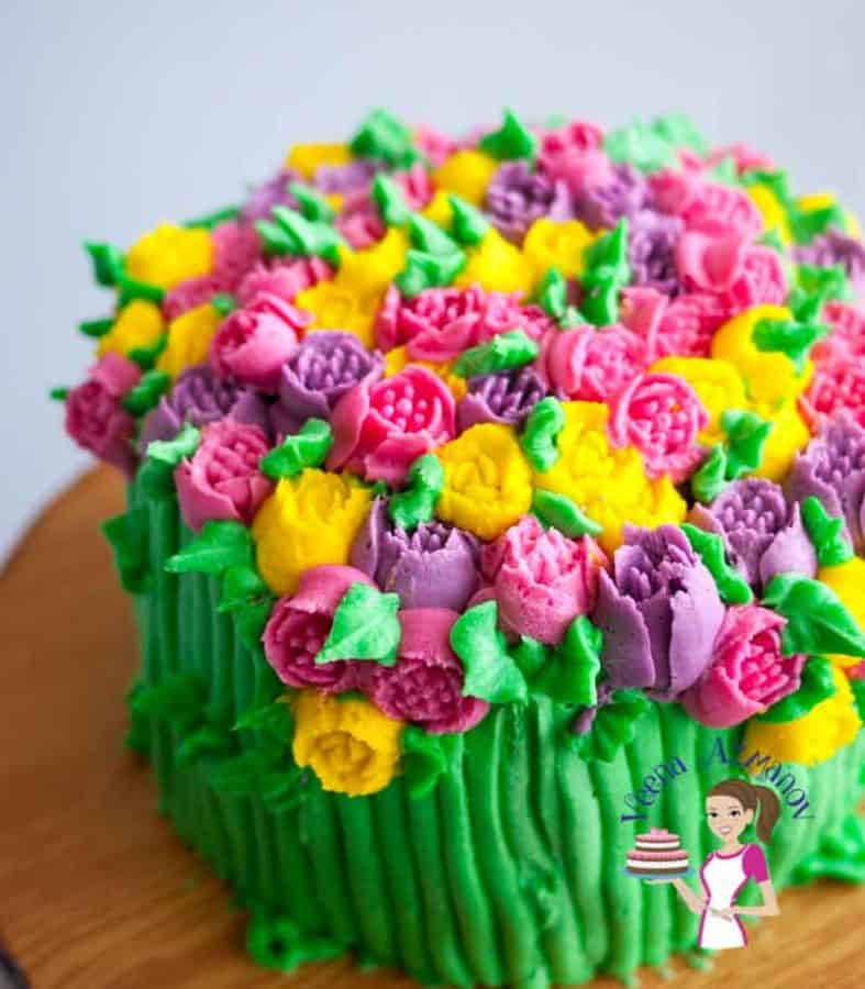 A cake decorated with colorful buttercream flowers.