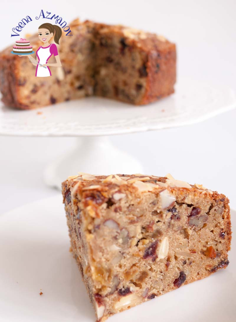 A classic slice of Rich Fruit Cake with the whole cake in the background. Perfectly baked Rich Fruit Cake for Christmas