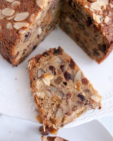 A slice of rich fruit cake on a plate.