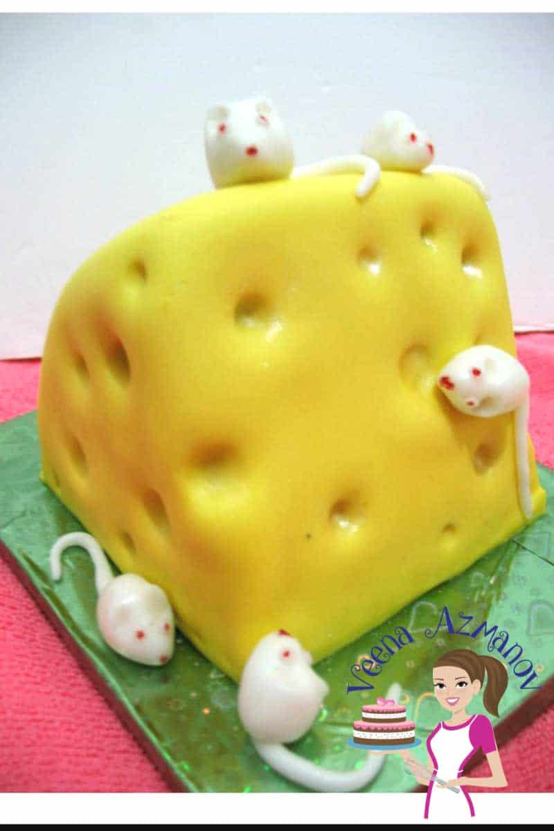 A cake decorated like a block of Swiss cheese with fondant mice.