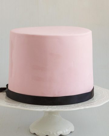 Fondant cake covered in pink fondant on a cake stand