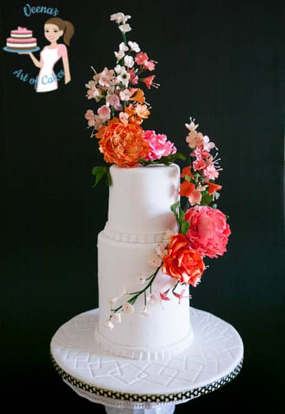 A white wedding cake with sugar flowers on top.