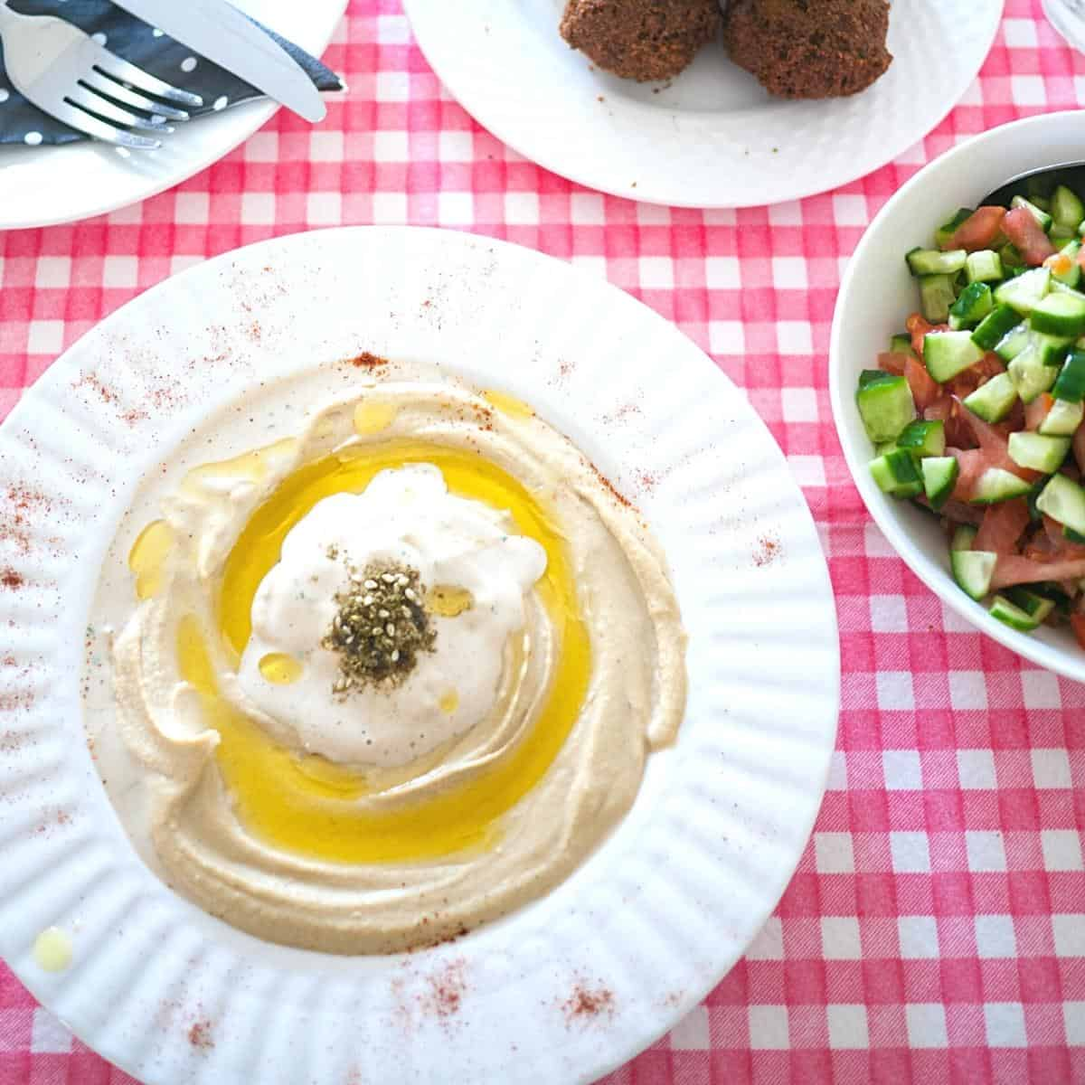 A shallow plate with served hummus and tahini sauce.