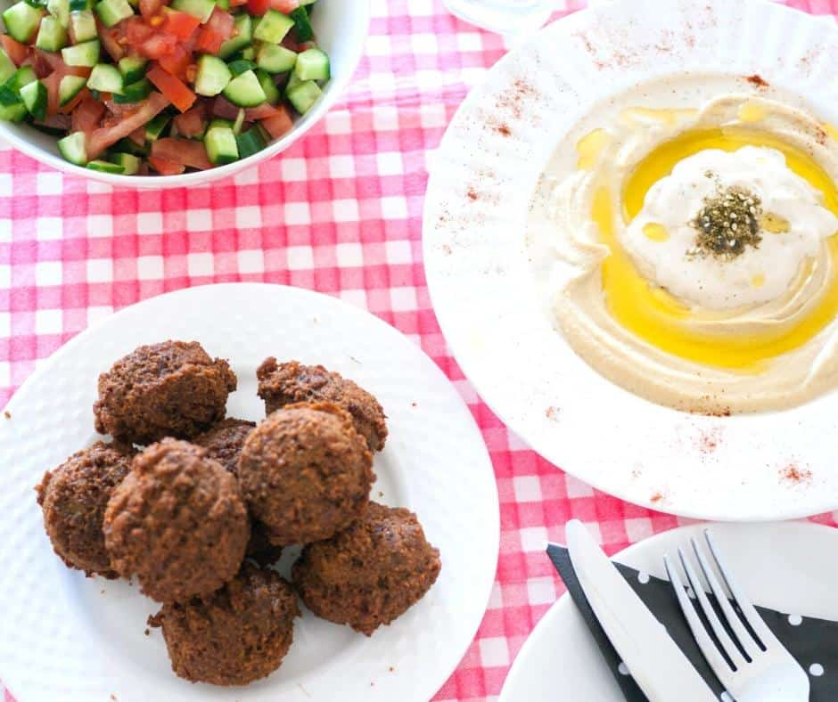 A plate of falafel balls next to a plate of hummus.