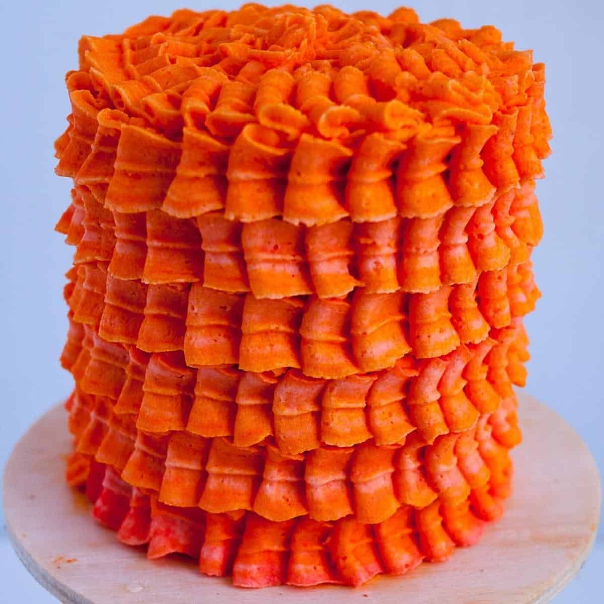 A frosted cake with orange Swiss meringue buttercream.