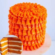 A frosted layer cake with orange Swiss meringue buttercream.