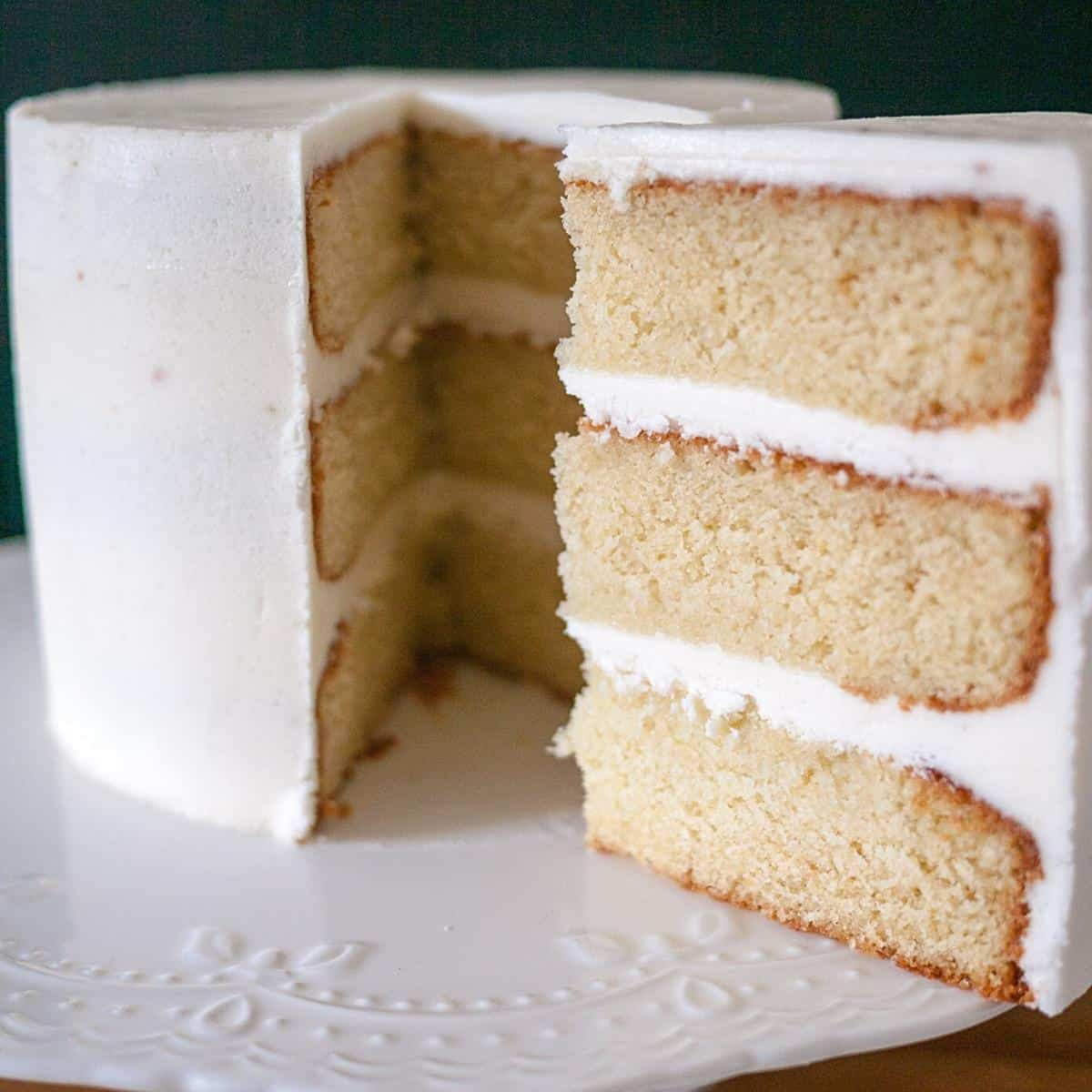 A sliced vanilla cake on a cake stand.