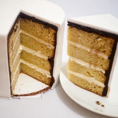 A cut vanilla cake on a cake board.