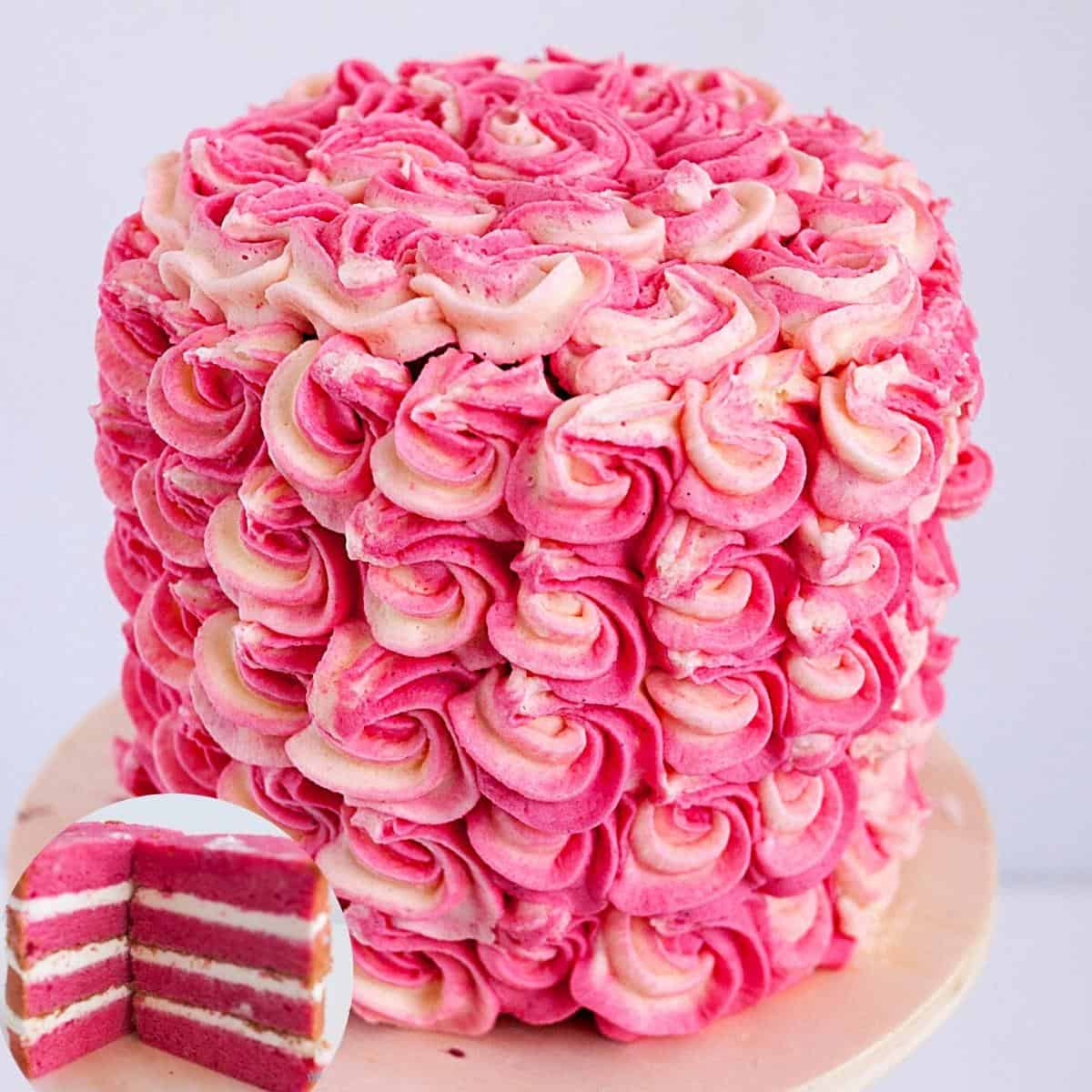 A frosted strawberry layer cake on a cake board.