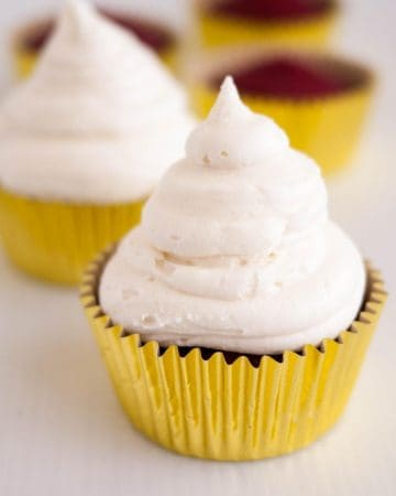 A cupcake with cream cheese frosting.