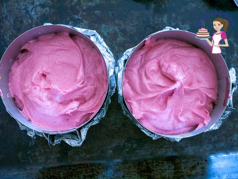 Strawberry cake batter in two baking pans.