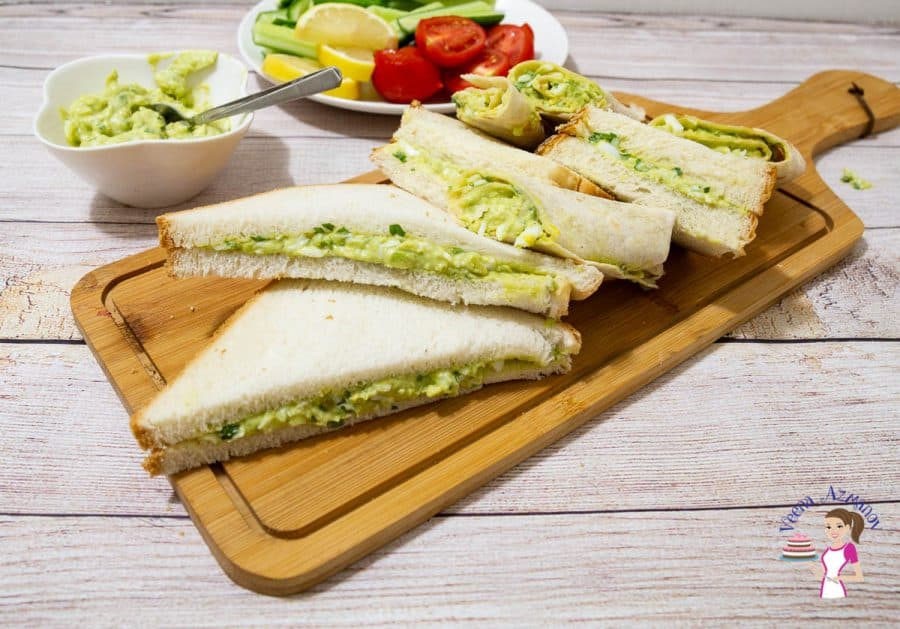 Avocado and egg sandwiches on a wooden board.