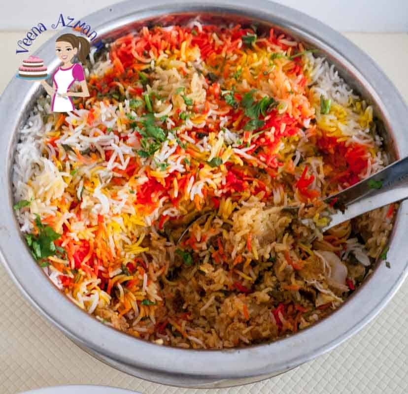 Top view of the pot of easiest Chicken Biryani you will ever make. Showing the colorful rice with yellow, red and orange with green cilantro leaves.