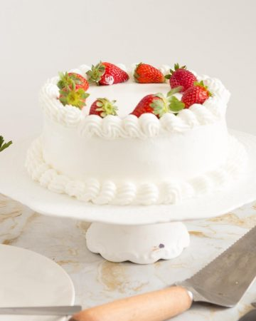 A whipped cream cake on a cake stand