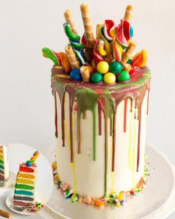Rainbow layer cake topped with candy and wafer