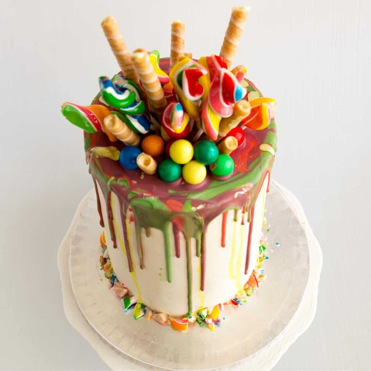 Rainbow layer cake topped with candy and wafers