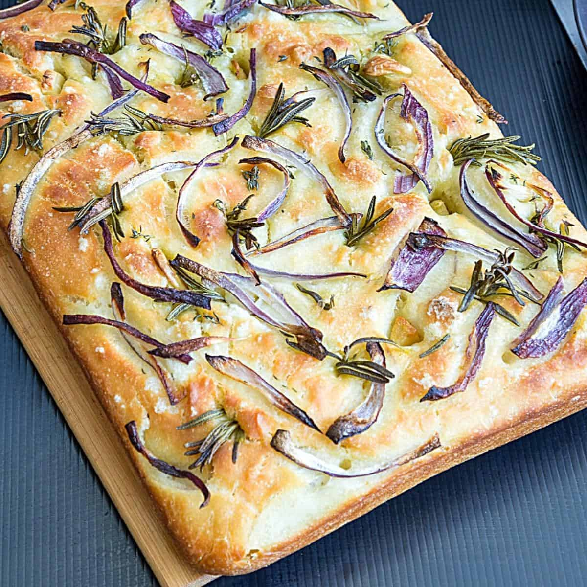 Italian focaccia with rosemary on a wooden board.