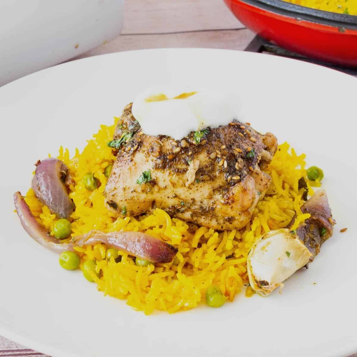 Chicken served over turmeric rice in a white plate.
