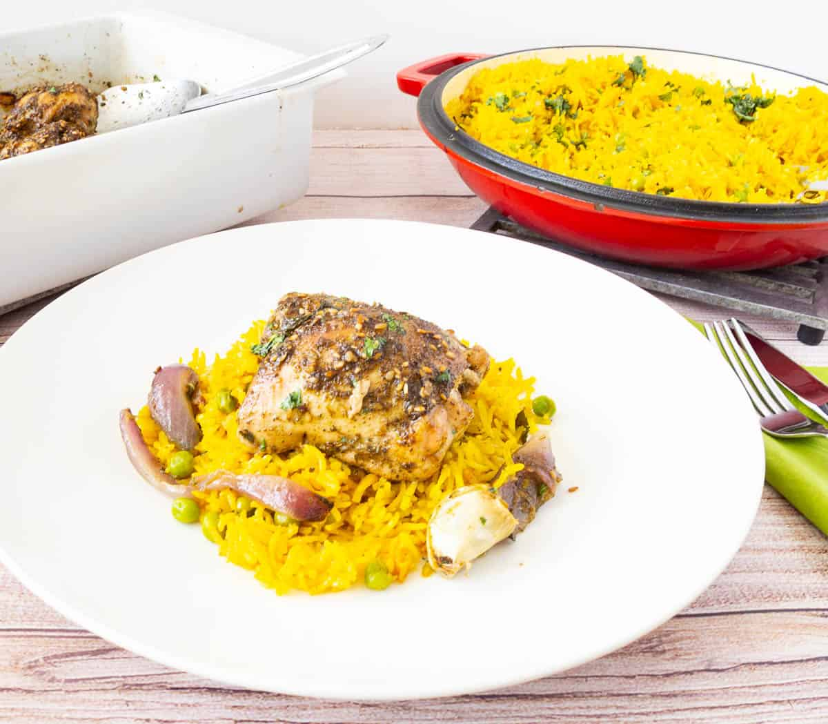 A plate of baked chicken with za'atar and yellow rice.
