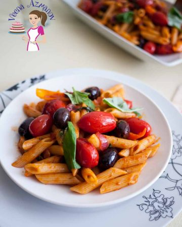 A plate of penne pasta with cherry tomatoes and olives.