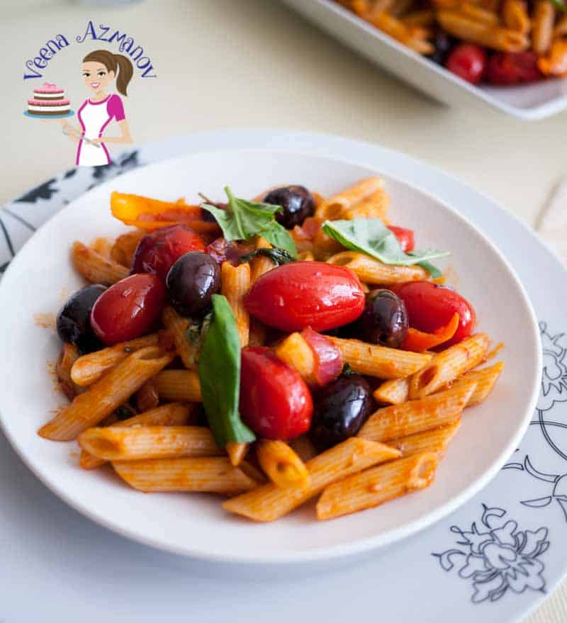 A plate of pasta with cherry tomatoes and olives.