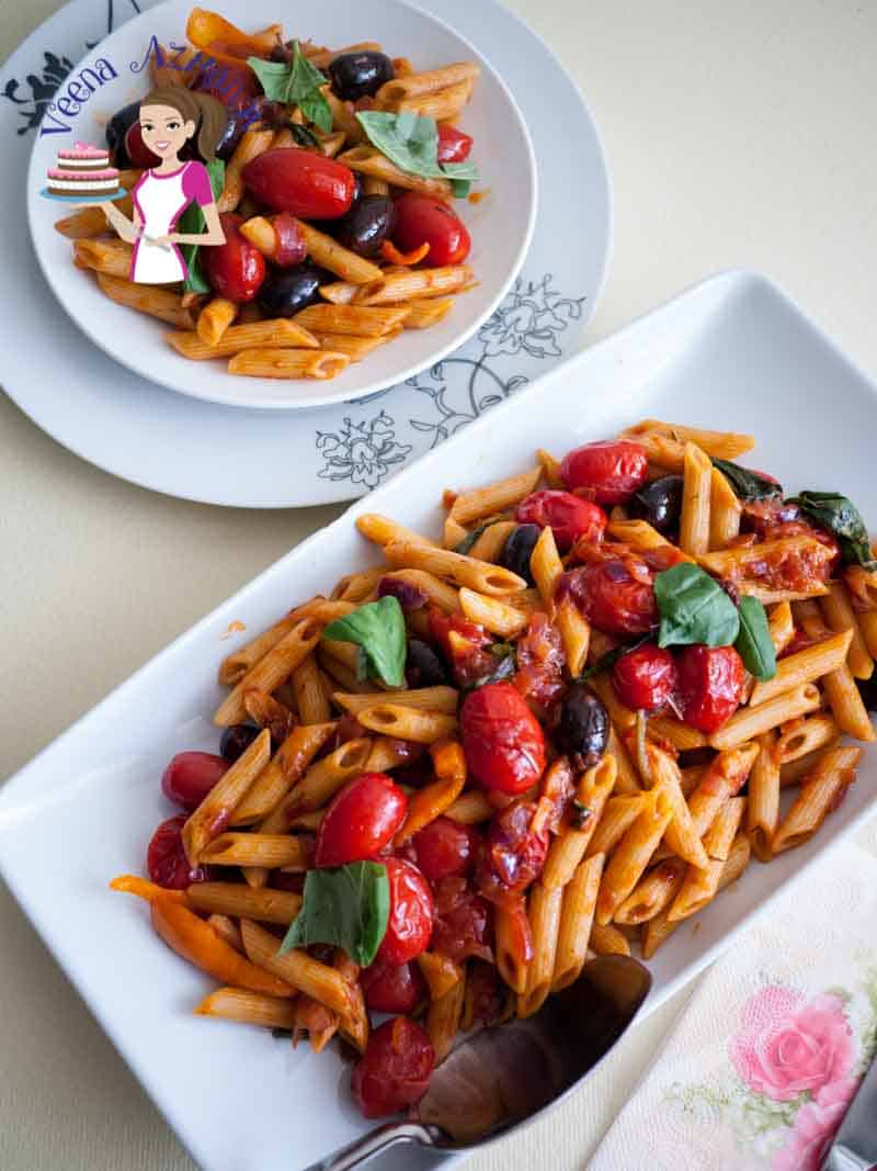 A serving dish with pasta with cherry tomatoes and olives.