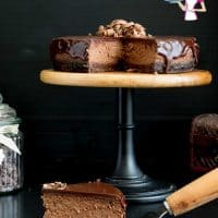 A perfectly baked chocolate flavored cheesecake on a cake stand ready to be served.