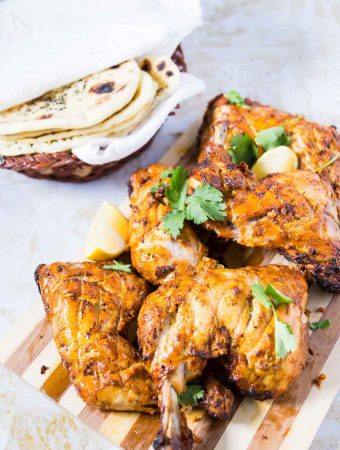 Traditionally made in a tandoor oven this classic Indian tandoori chicken can be easily made in a conventional oven at home. This simple, easy and effortless recipe for oven baked tandoori chicken is marinated in yogurt and exotic Indian spices then baked until succulent, golden and delicious that just melts in the mouth.