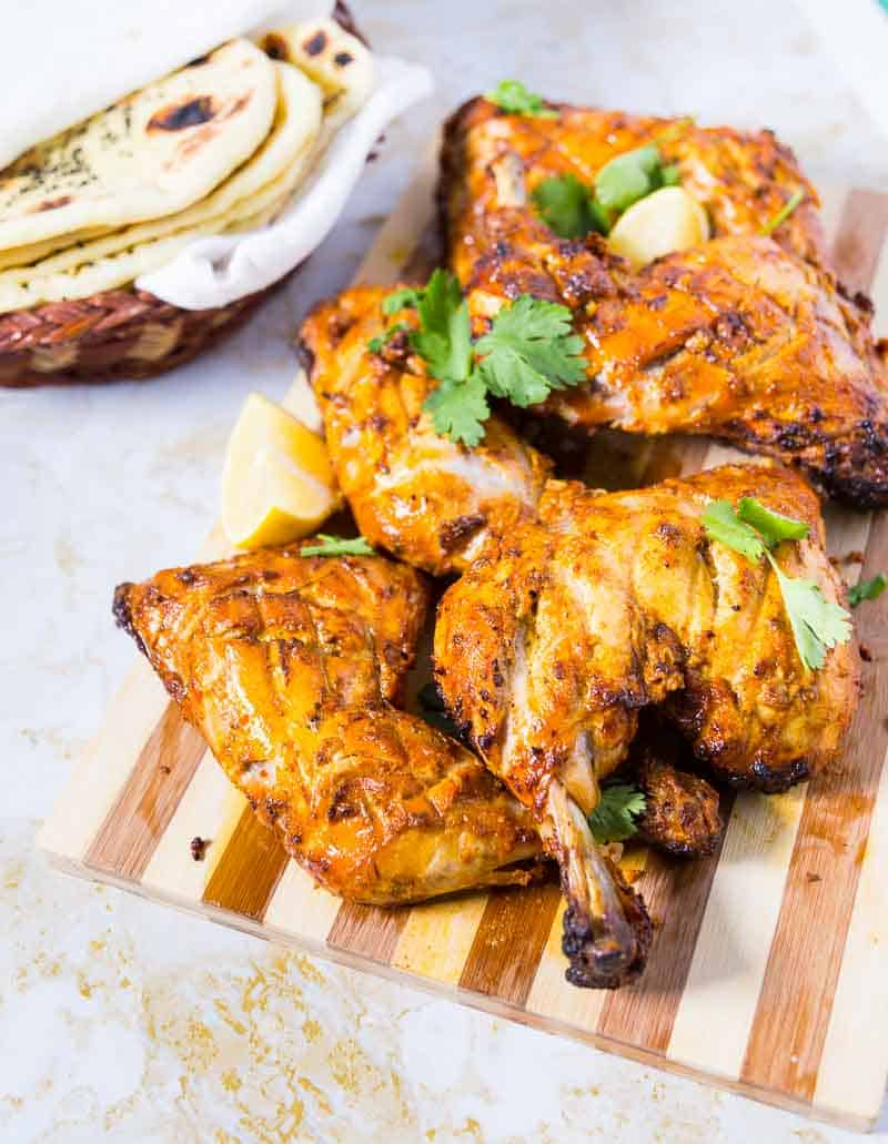 Tandoori chicken on a wooden board.