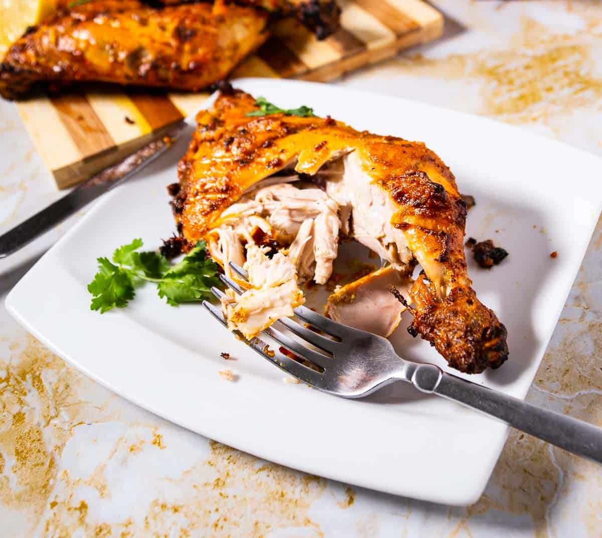 A baked tandoori chicken quarter on a white plate.