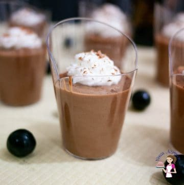 A glass of mousse topped with whipped cream