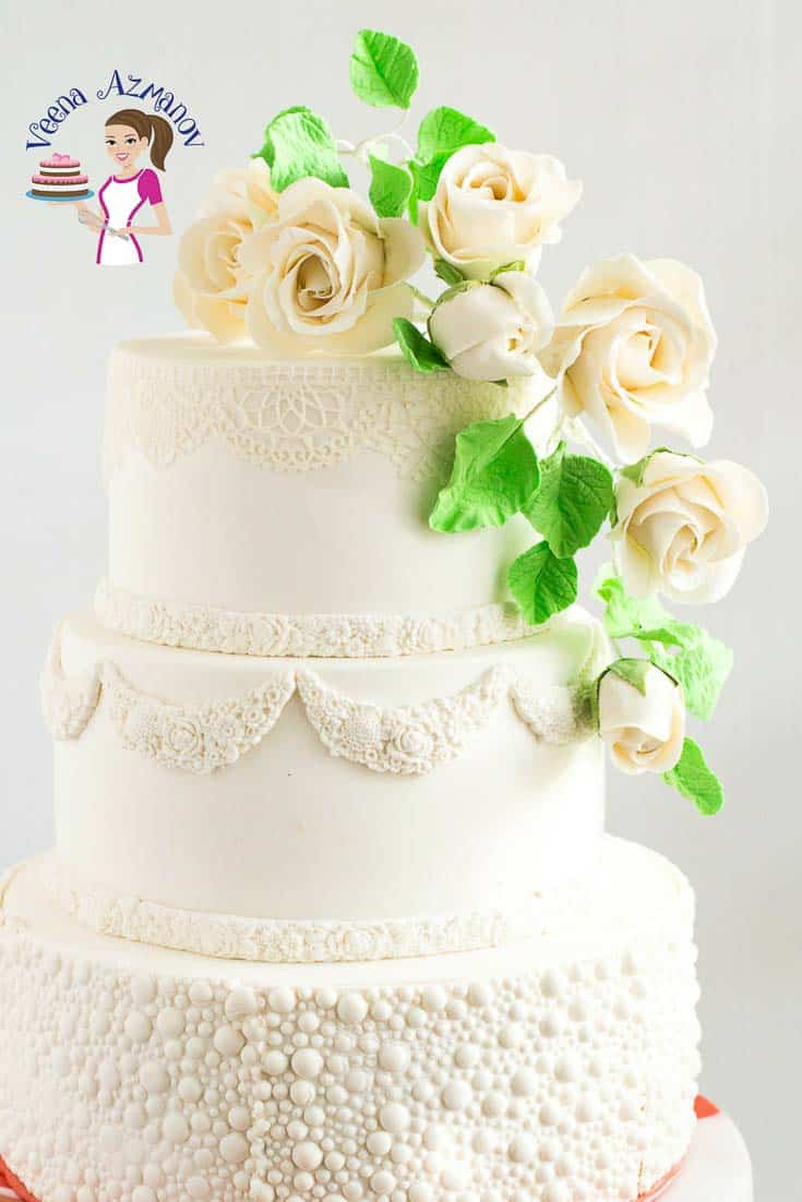 A wedding cake with white gum paste roses.