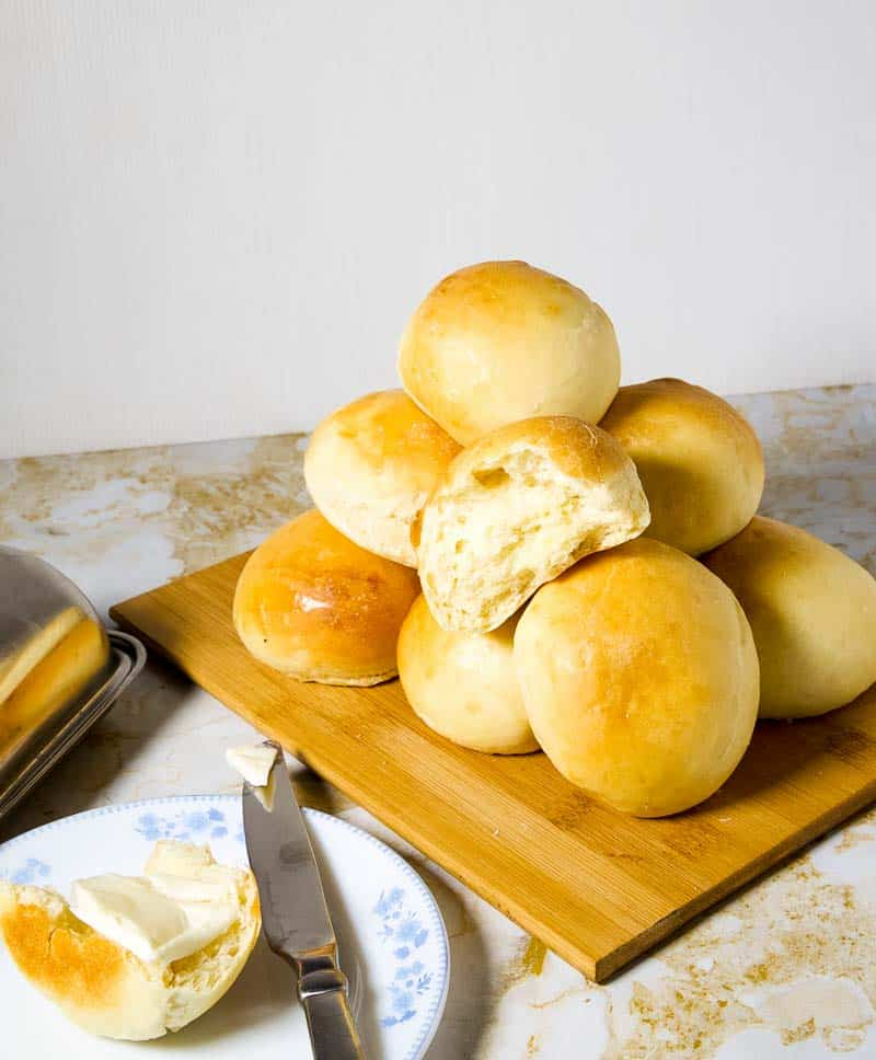 A Pile of dinner rolls on a board - freshly prepared soft dinner rolls with one broken off and buttered