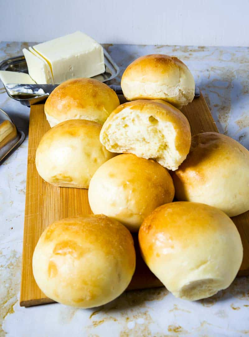 A scattered pile of homemade soft dinner rolls with one broken showcasing the soft light and fluffy bread.
