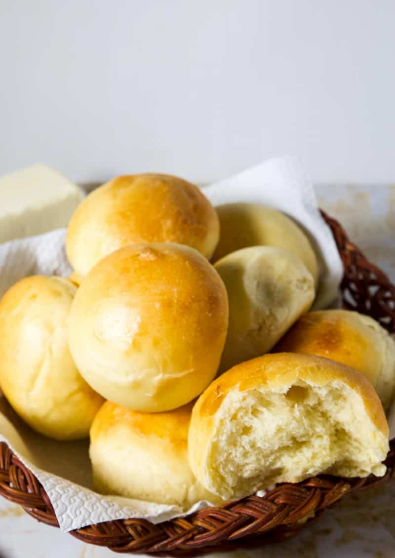 A close up shot of the homemade soft dinner rolls in a basket with one broken off so you can see the texture of the light and fluffy bread roll