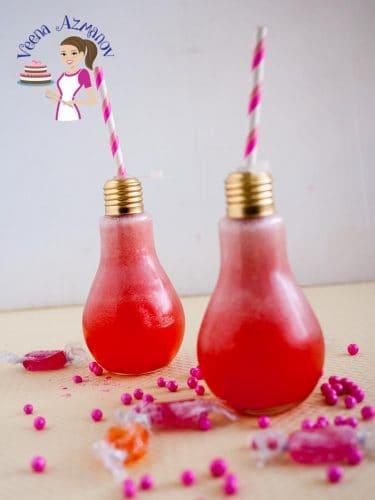 Strawberry lemonade in a glass shaped like a light bulb.