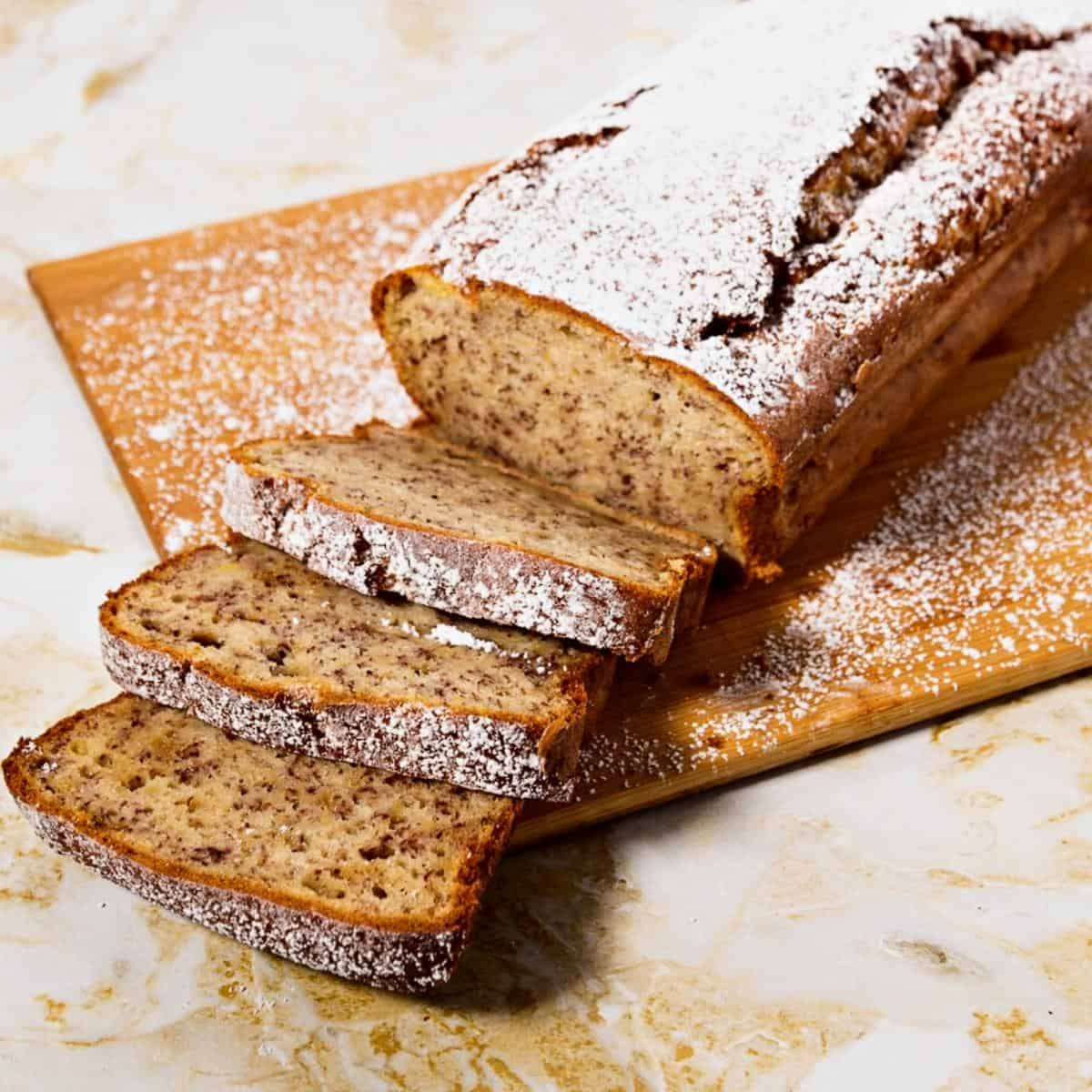 A sliced banana loaf cake on a wooden board.