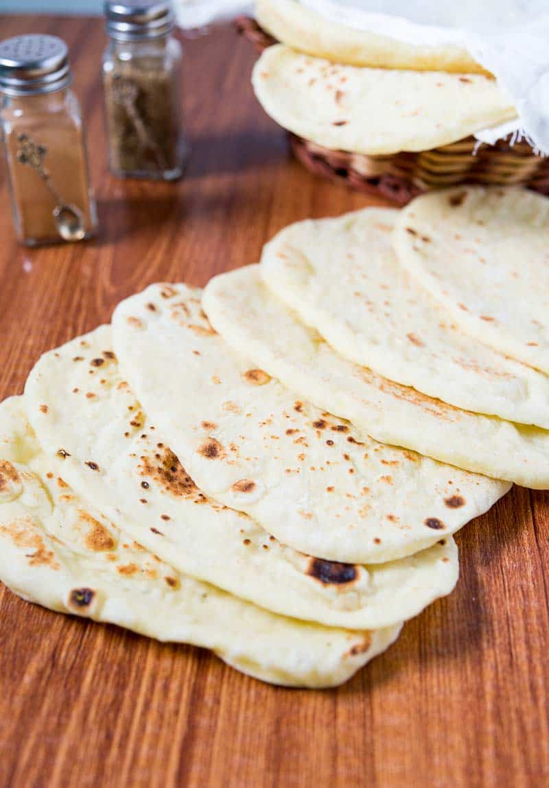 A close up of the homemade Naan bread laying flat on the table. Simple, easy and effortless recipe that's made on the stovetop