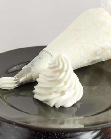 A whipped cream swirl on a black plate
