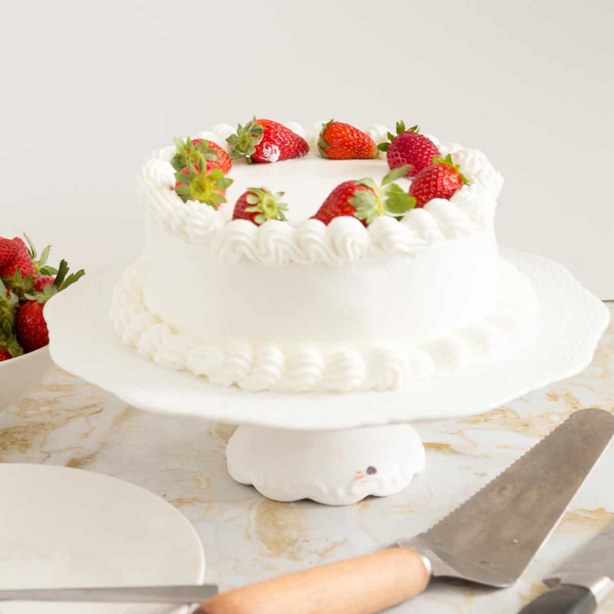 A whipped cream frosted strawberry cake.