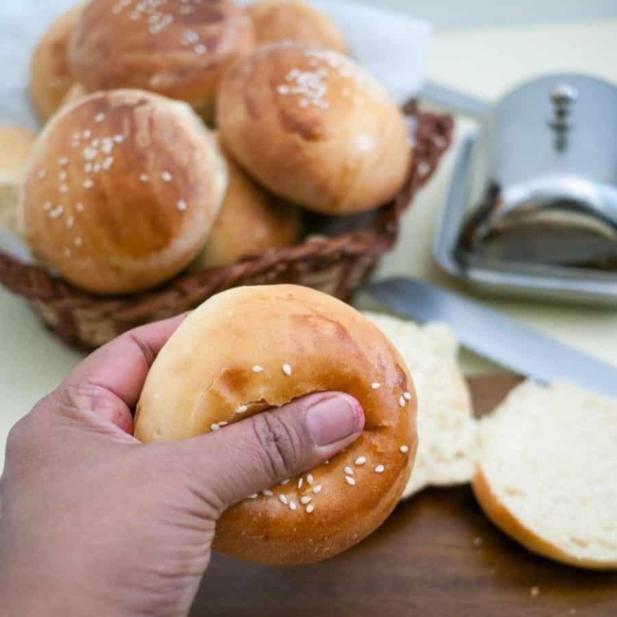 A person holding a soft hamburger bun.