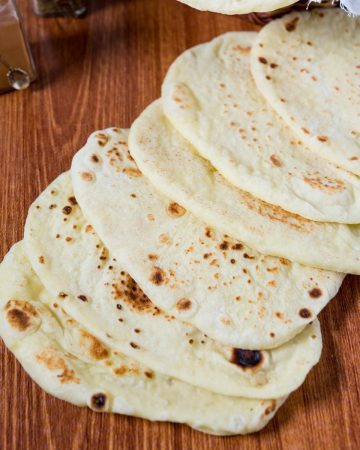 A stack of naan breads on the table.