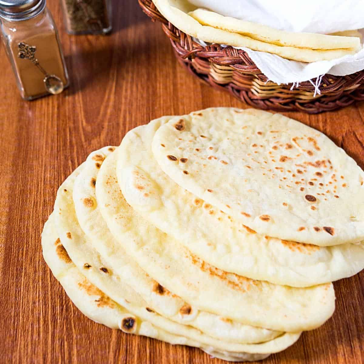 A stack of naan bread on a table.