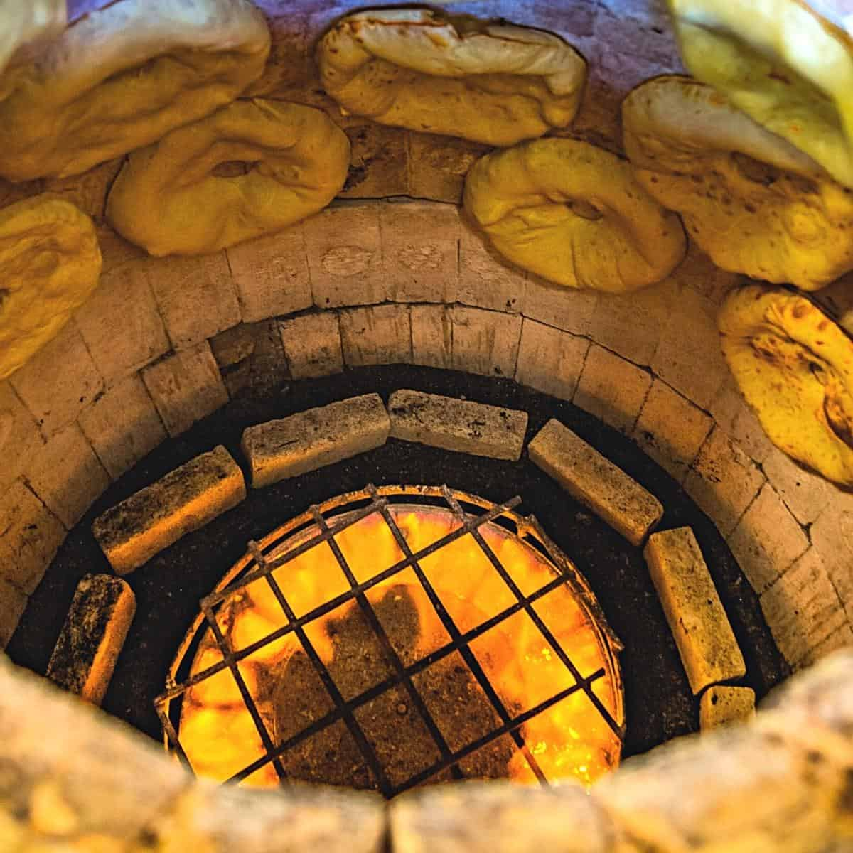 A tandoor with naan stuck to them.