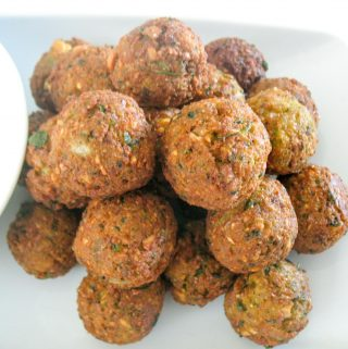 A stack of falafel balls on a plate.