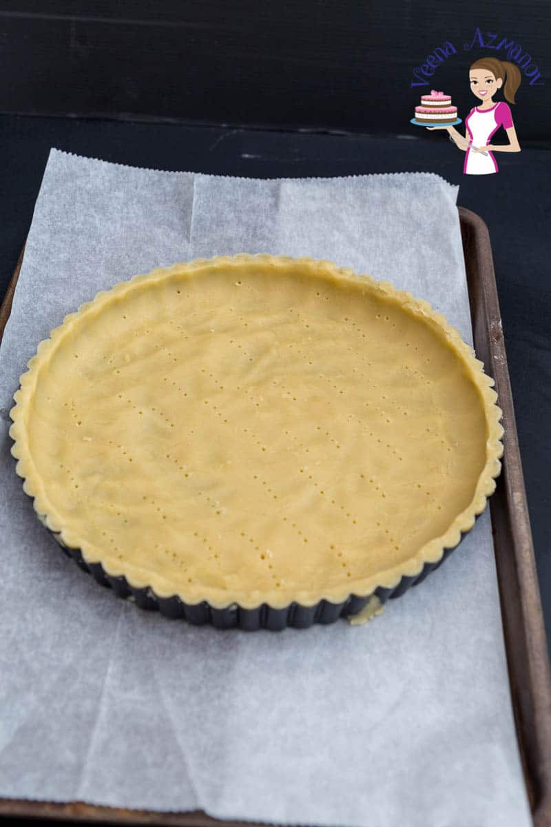 An unbaked tart crust in a tart pan.
