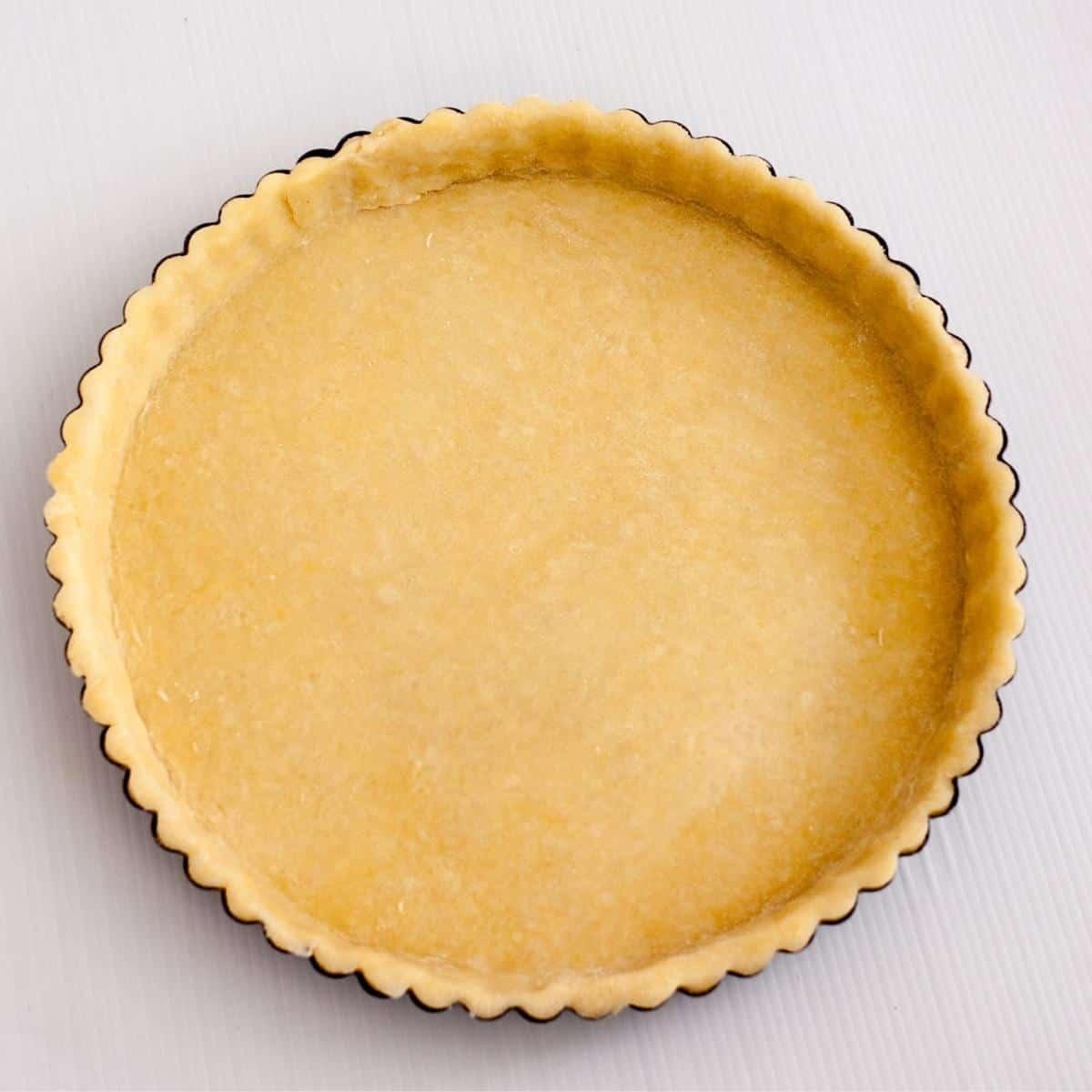An unbaked tart crust in a tart pan.